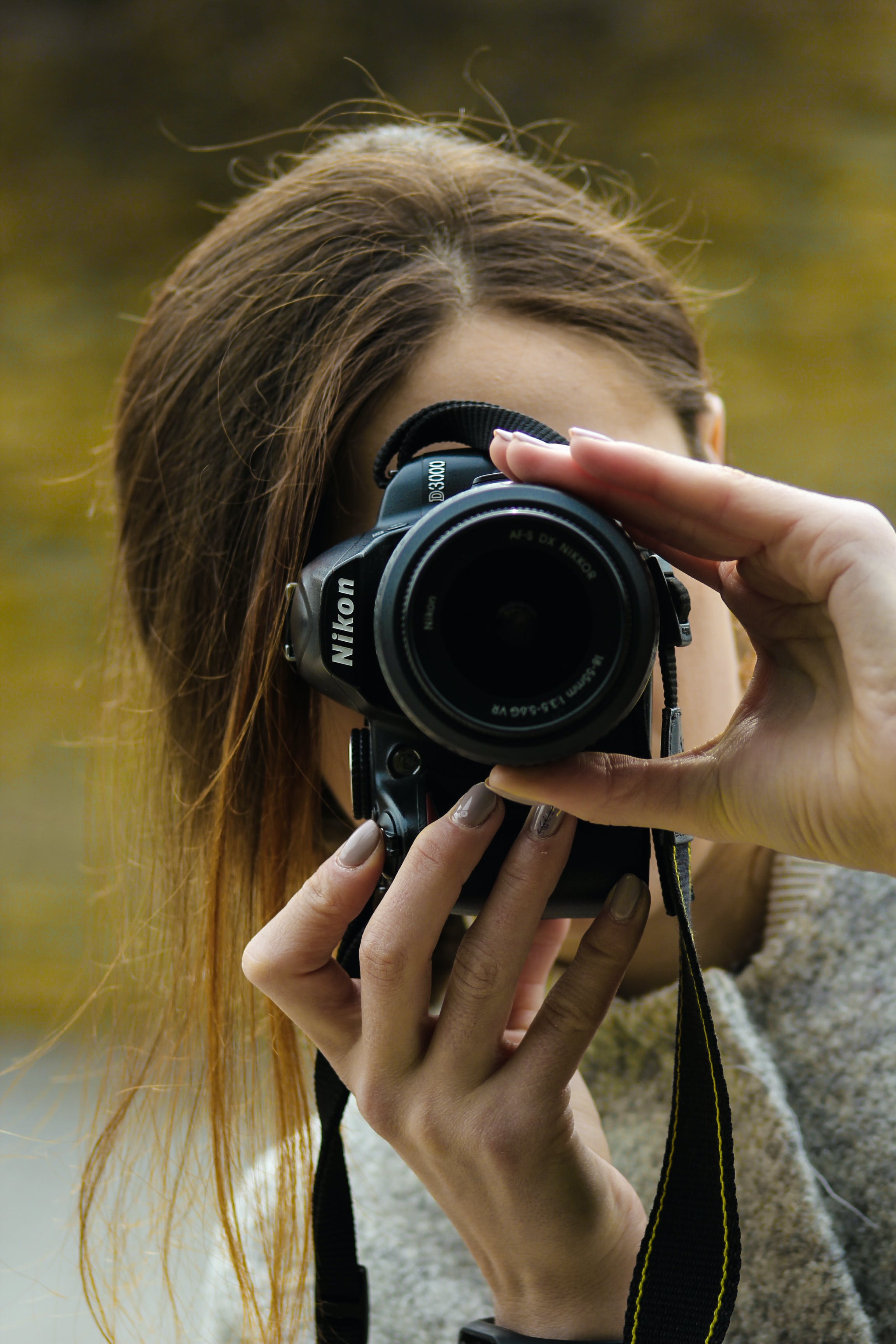 Close-up Photography of Woman Using Black Nikon Dslr Camera