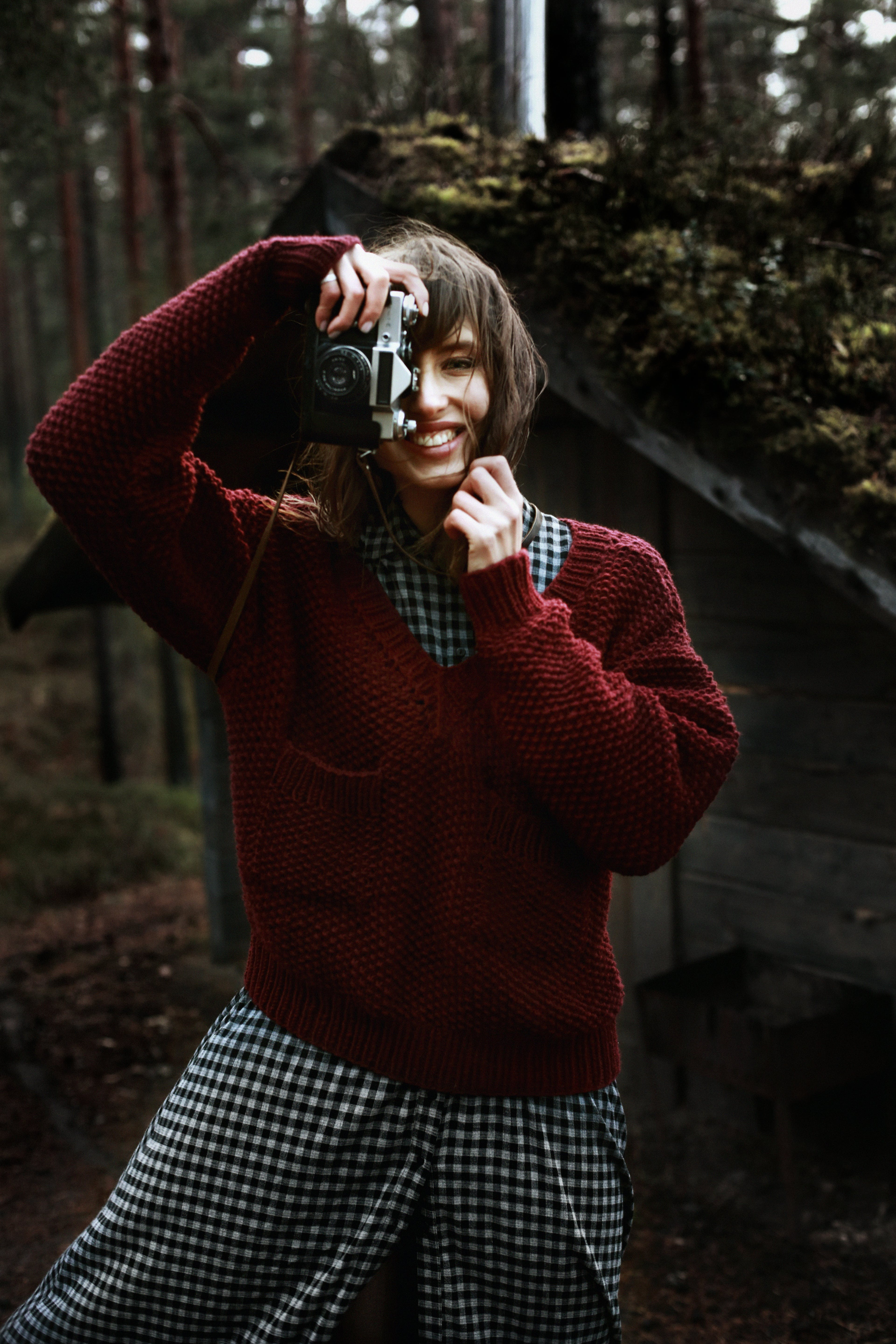 Smiling Woman Wearing Red Sweater Holding Camera