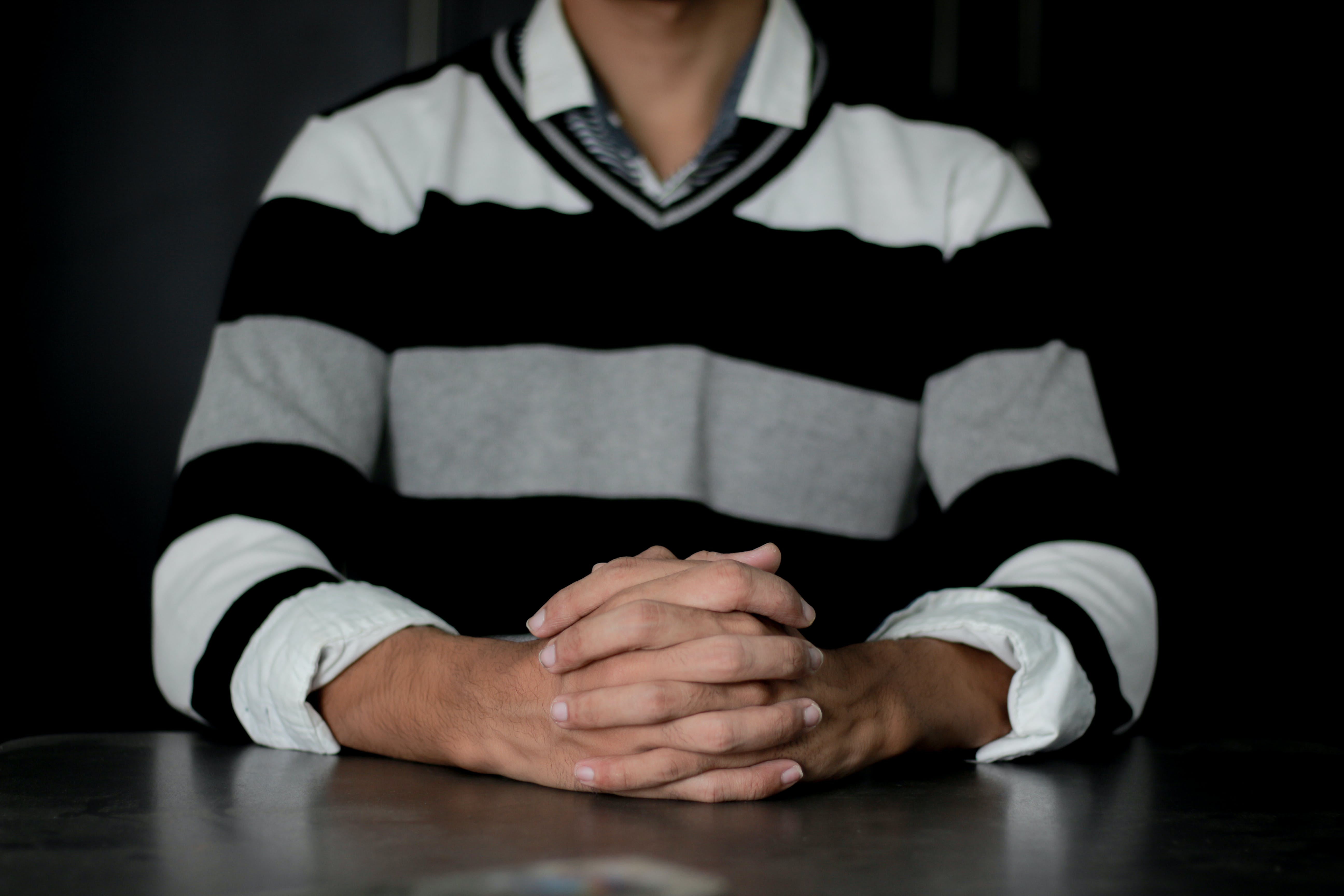Person Wearing White and Black Striped Sweater Sitting