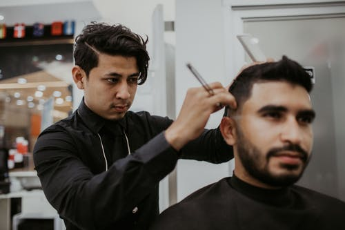 Man Cutting Another Man's Hair