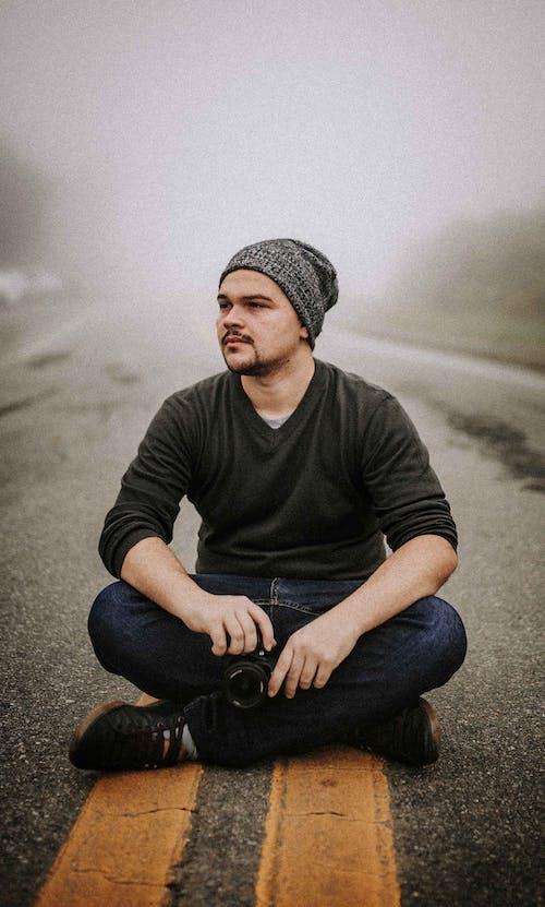 Man Sitting On Asphalt Road