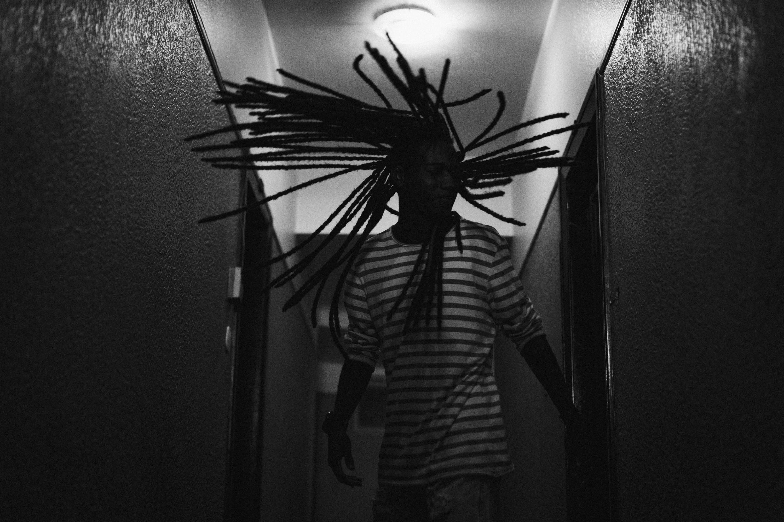 Grayscale Photography of Man Whipping His Dreadlocks Hair