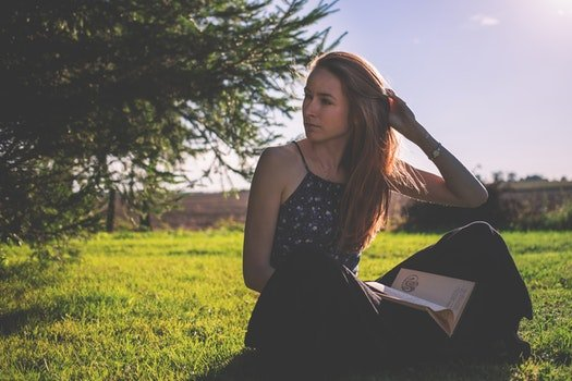 Woman in Black Tank Top and Holding Brown Book Sitting on Grass Under Clear Sunny Sky