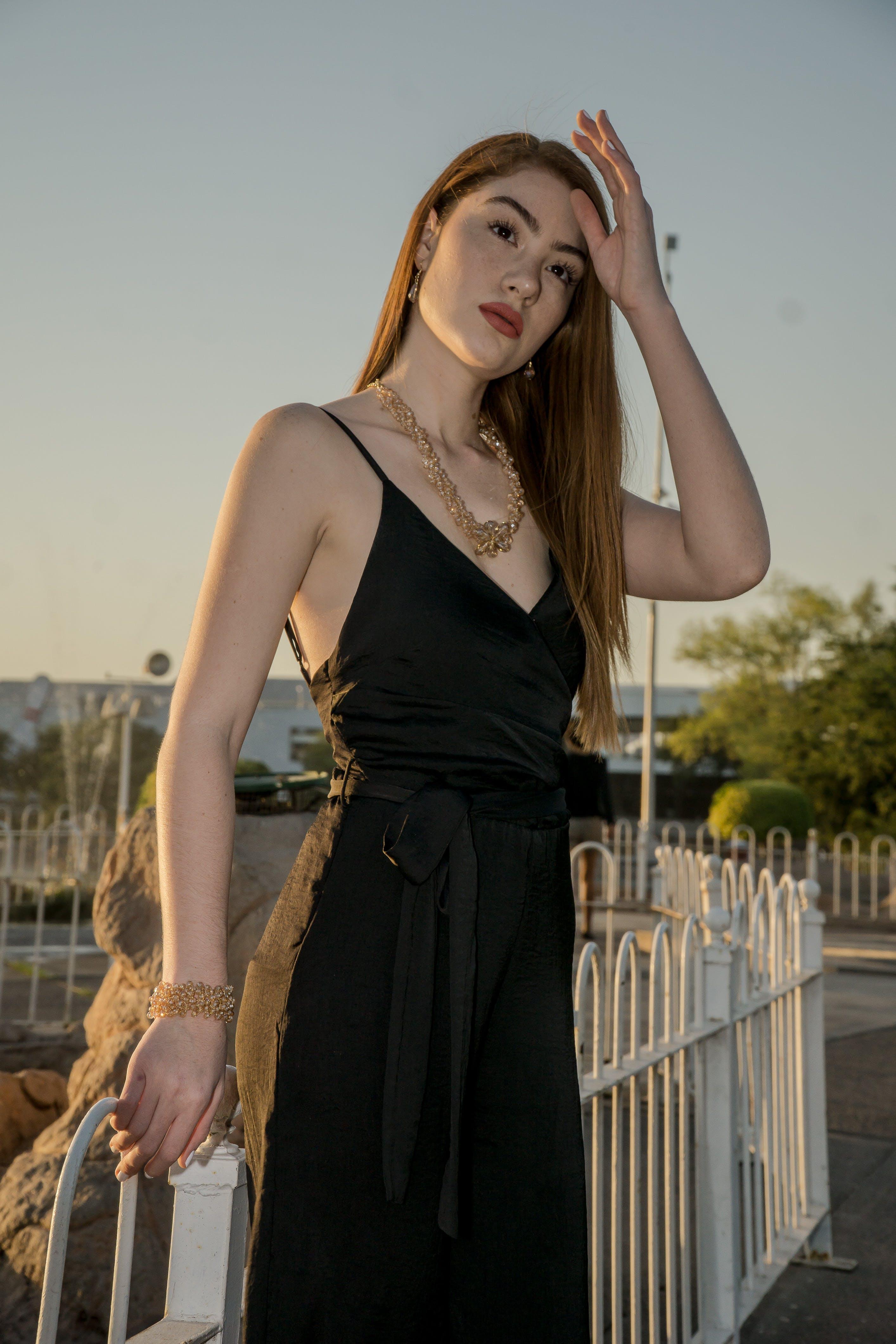 Woman Standing Near White Metal Fence