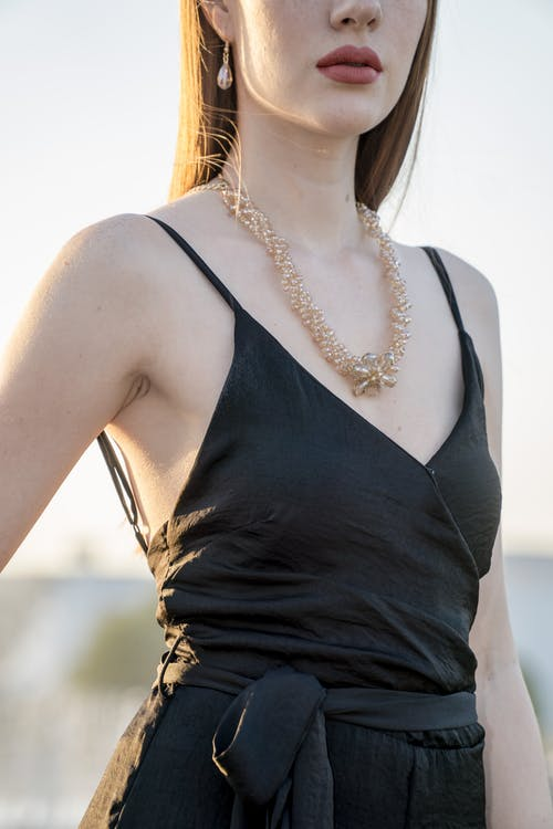 Woman Wearing Black Spaghetti Strap Dress and Gold-colored Necklace