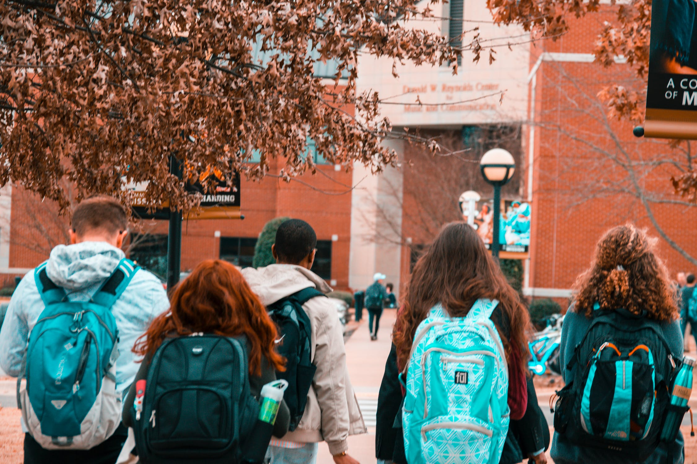 College students with backpacks walking on campus away from the camera. Photo by pexels user Stanley Morales. Used Courtesy of pexels.com.
