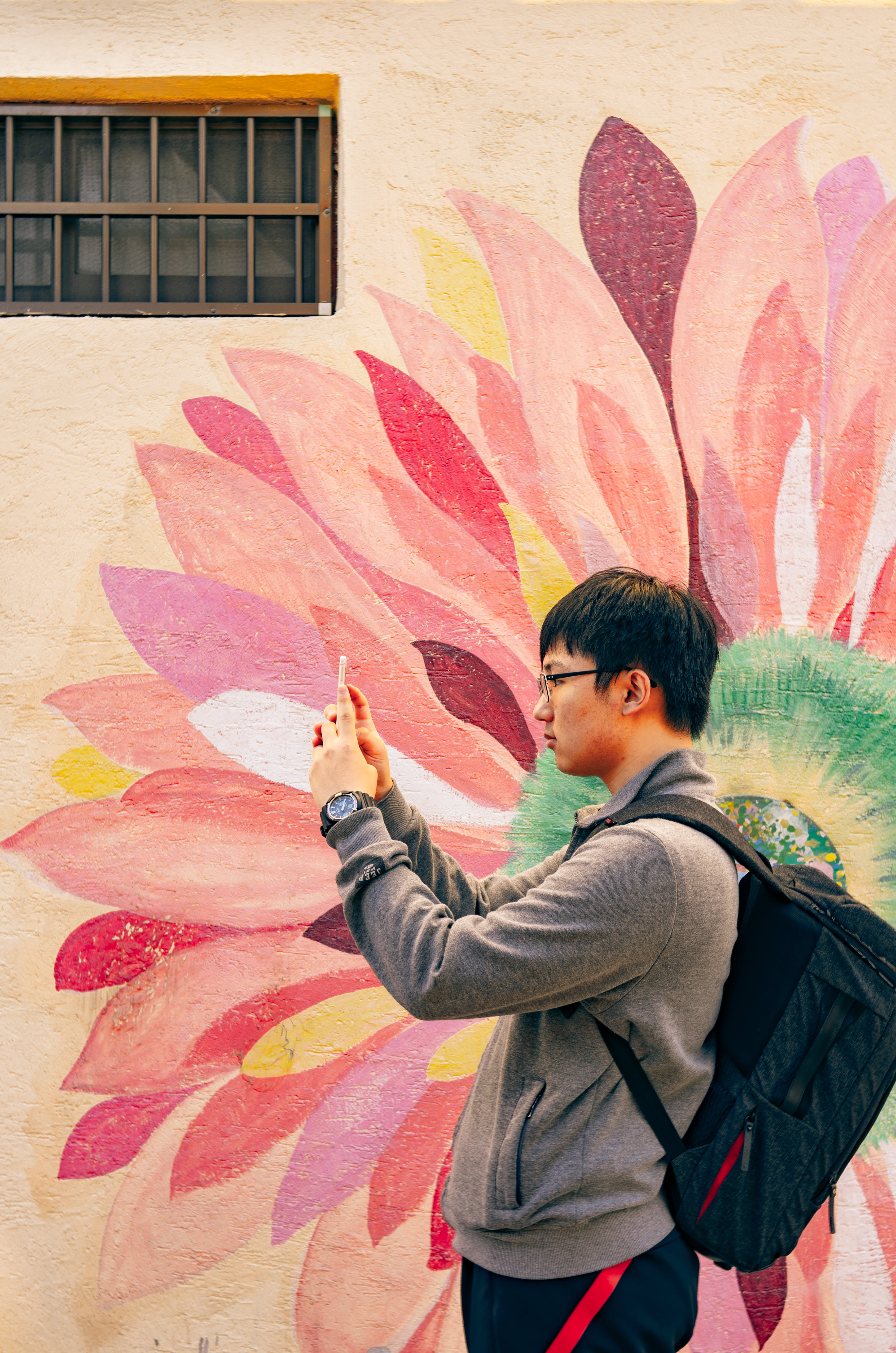 Man Using Smartphone Beside Floral Wall