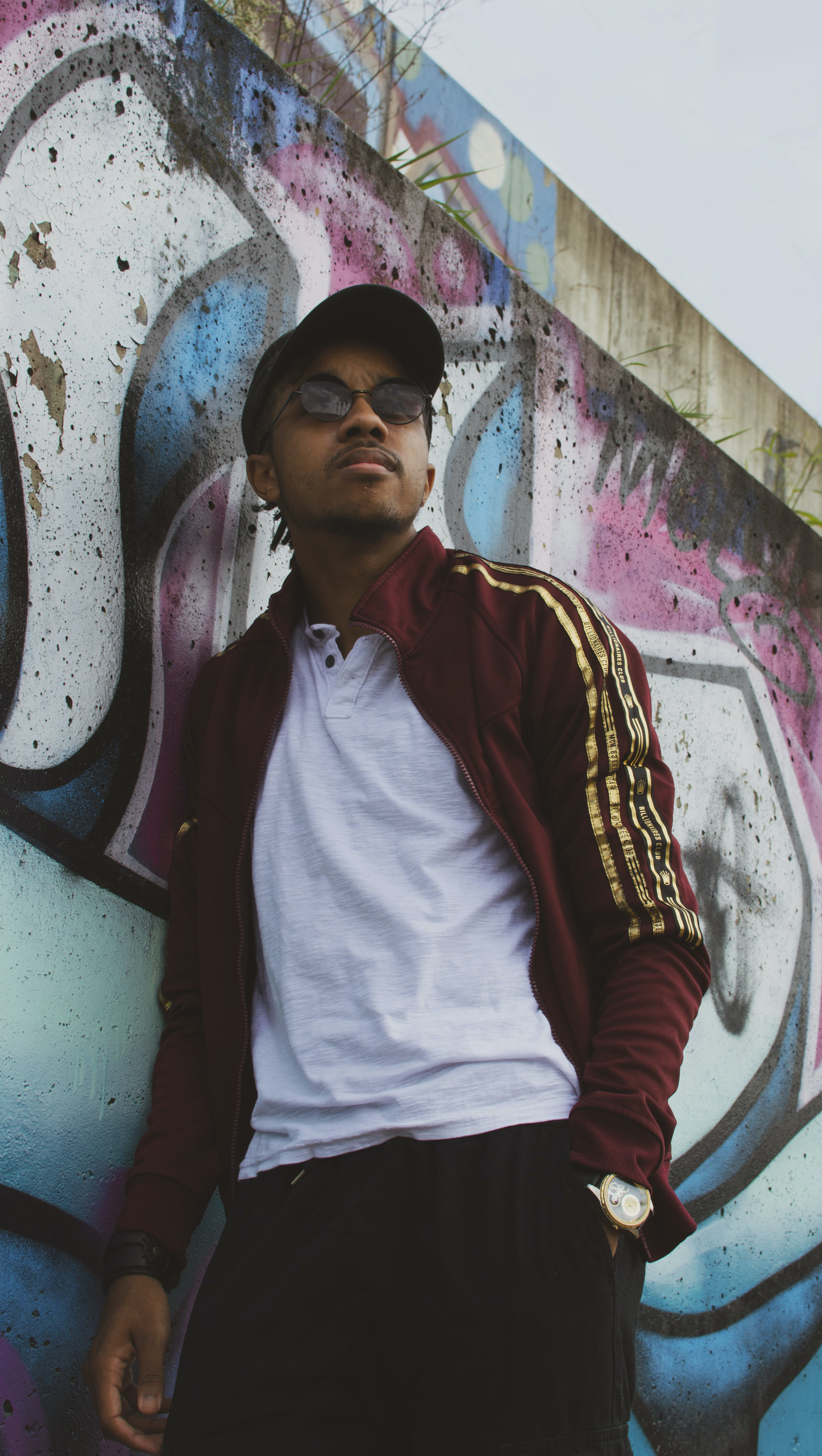 Man in Maroon Jacket Leaning Beside Wall