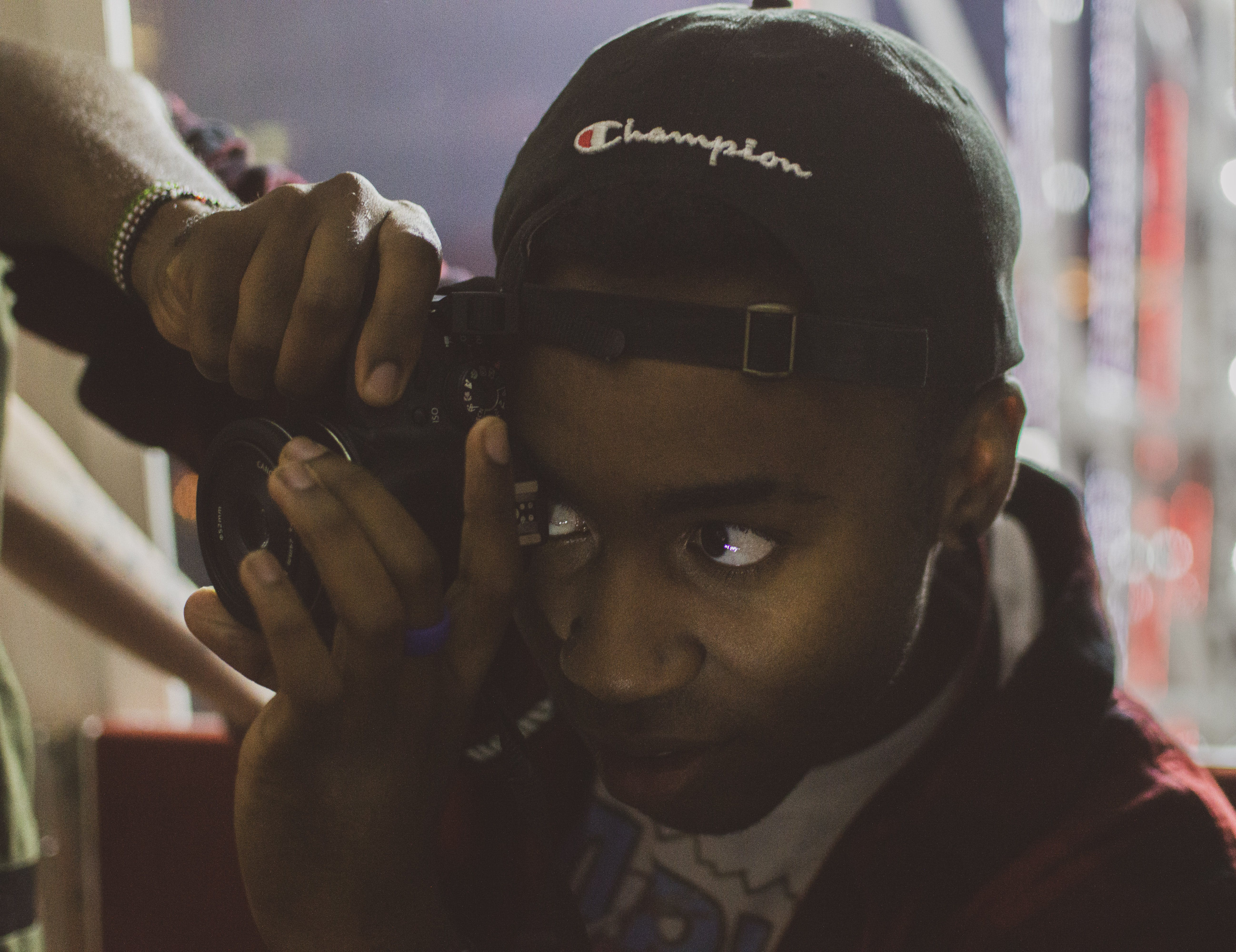 Person Holding Camera Wearing Black Champion Cap