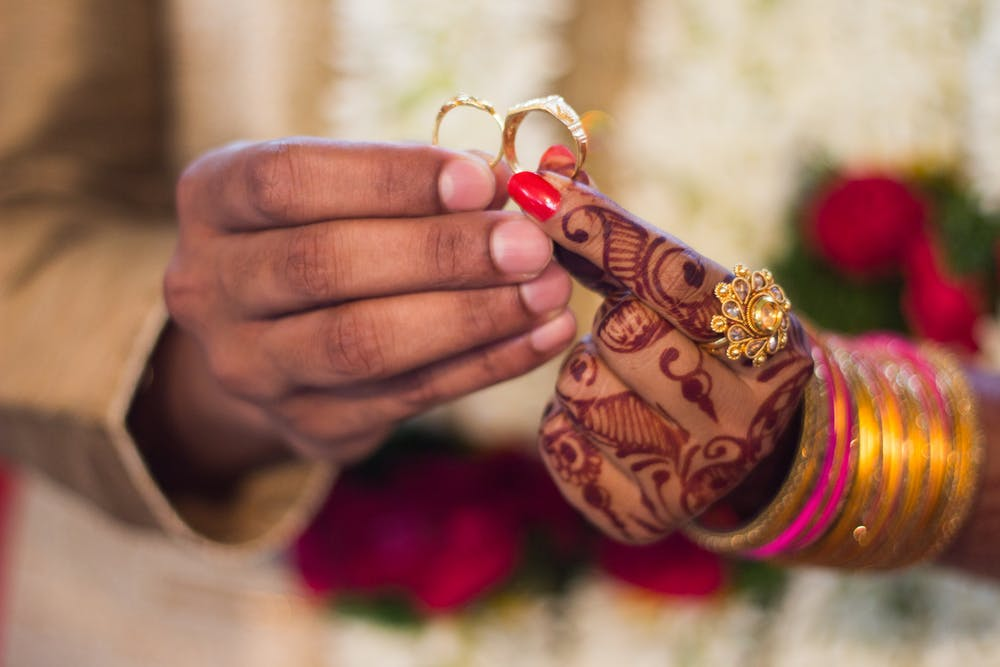 Man and woman holding wedding rings. | Photo: Pexels