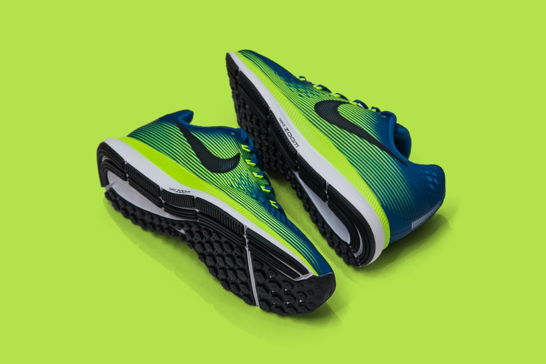 From above of colored sneakers with blue and green surface and green and white and black sole for comfortable moving around streets against green background