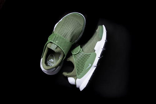 Top view of sneakers with khaki breathable surface and rubber inserts for comfortable securing feet and white soles and back parts placed on black glance background