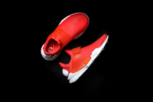 Top view of modern pair of sneakers with red texture and rubber inserts holding right form comfortable for foot and white soles placed on black glance surface
