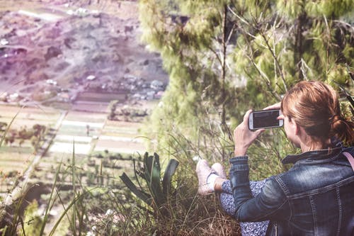 Woman Holding Smartphone Overlooking Plain Field