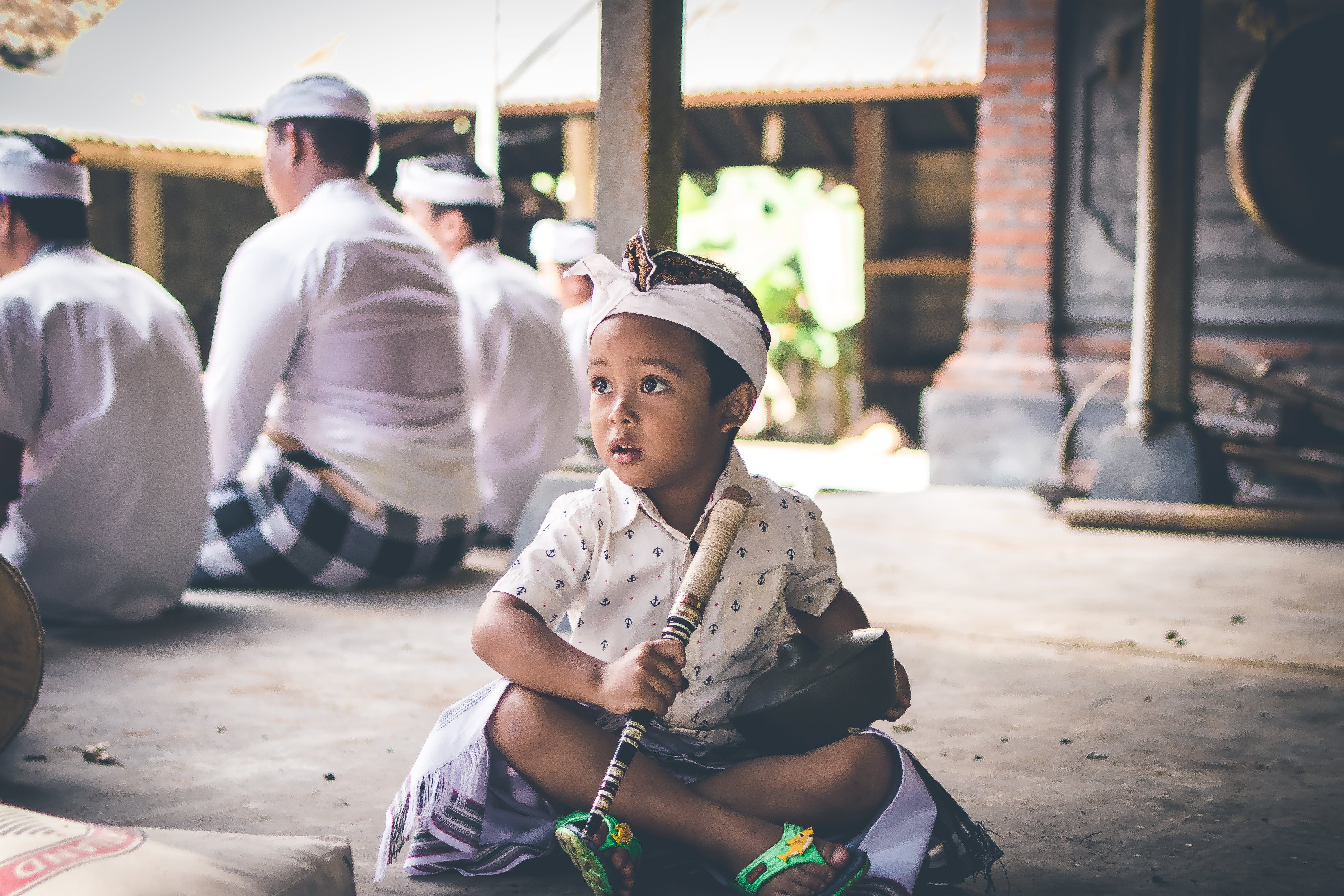 Boy Holding Flute While Sitting on Floor