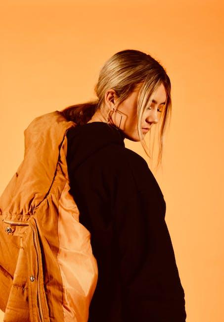Woman wearing black coat holding brown jacket