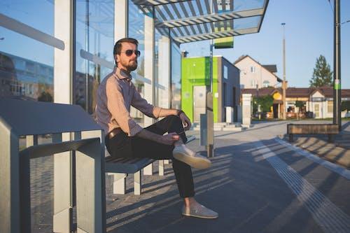 Man Wearing Sunglasses Sitting at Bus Stop during Daytime