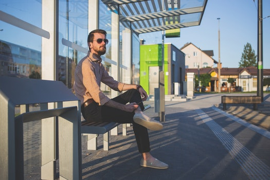 Man Wearing Sunglasses Sitting at Bus Stop during Daytime