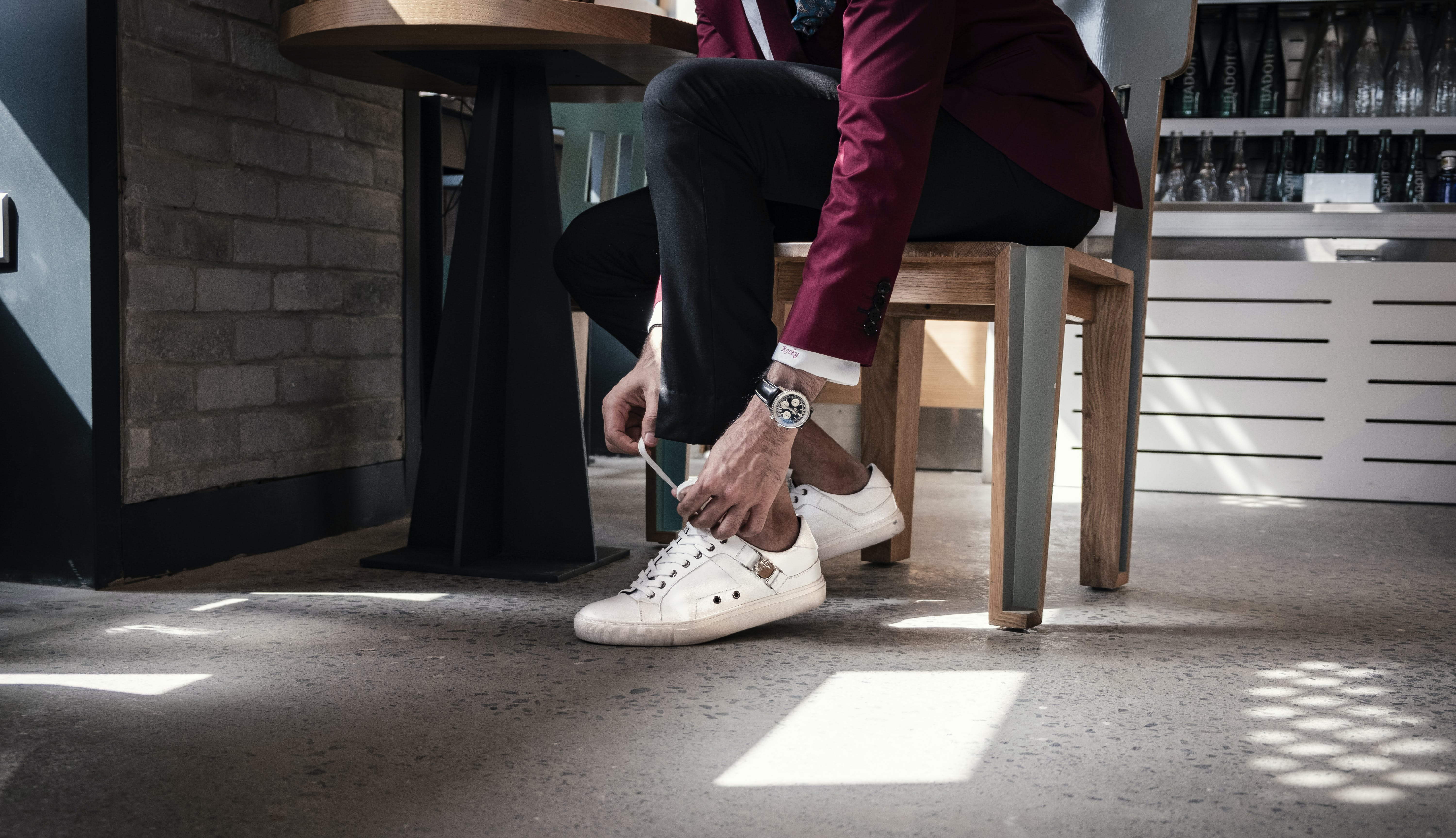 Man Sitting on Chair While Holding Shoe Lace