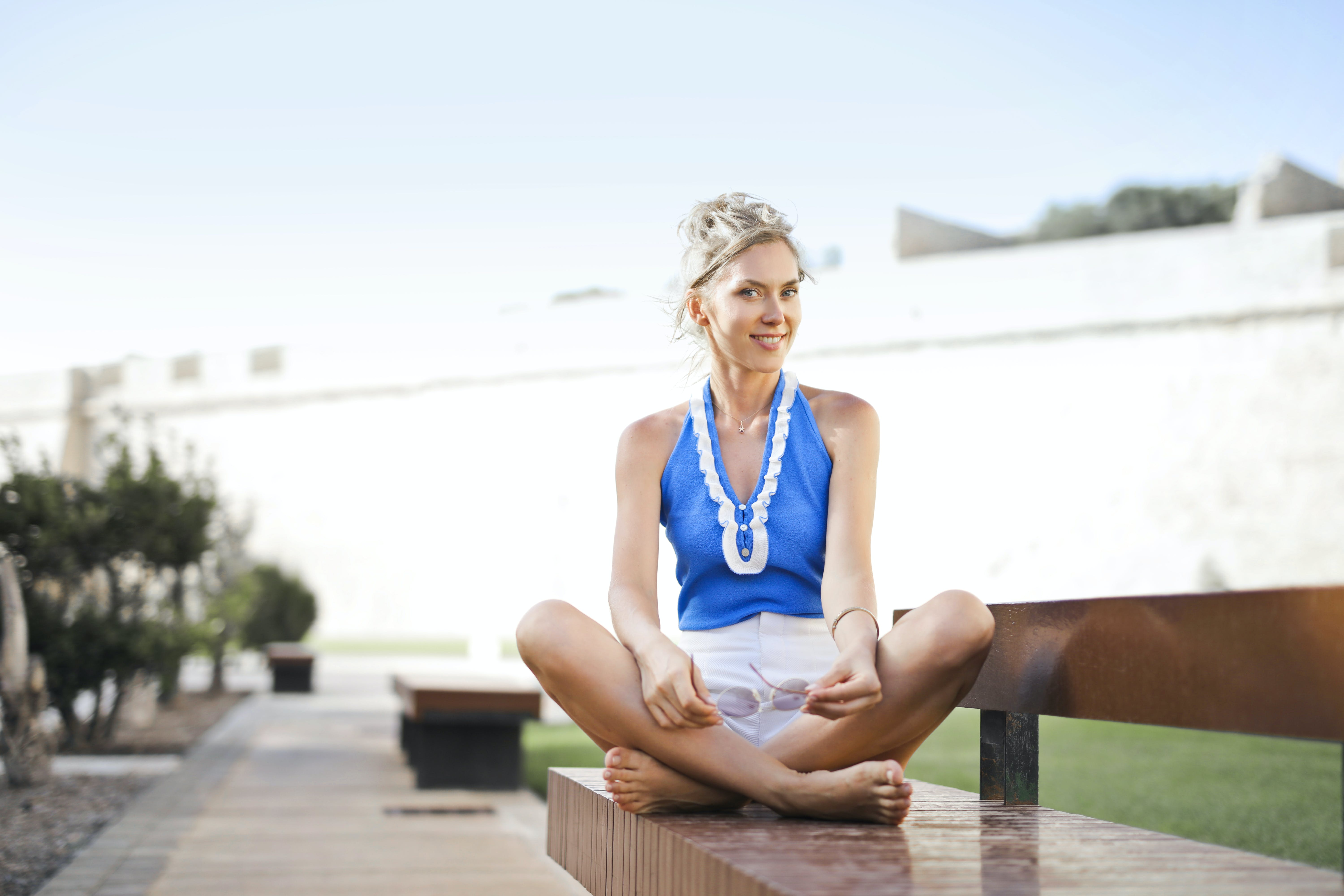 Woman Sitting on Bench Near White Wall Under White Sky