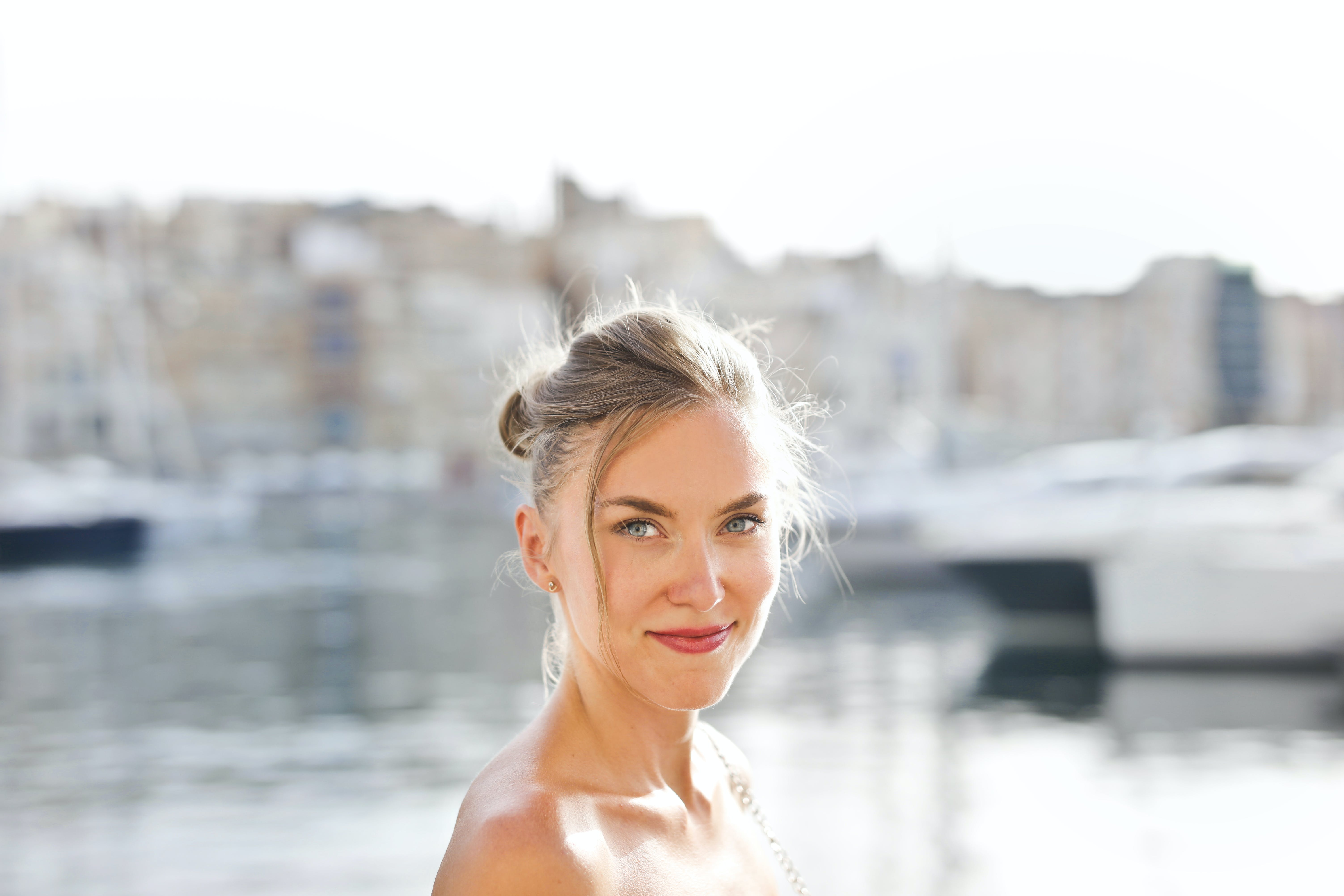 Smiling Woman Standing Near Body of Water Under Blue Sky