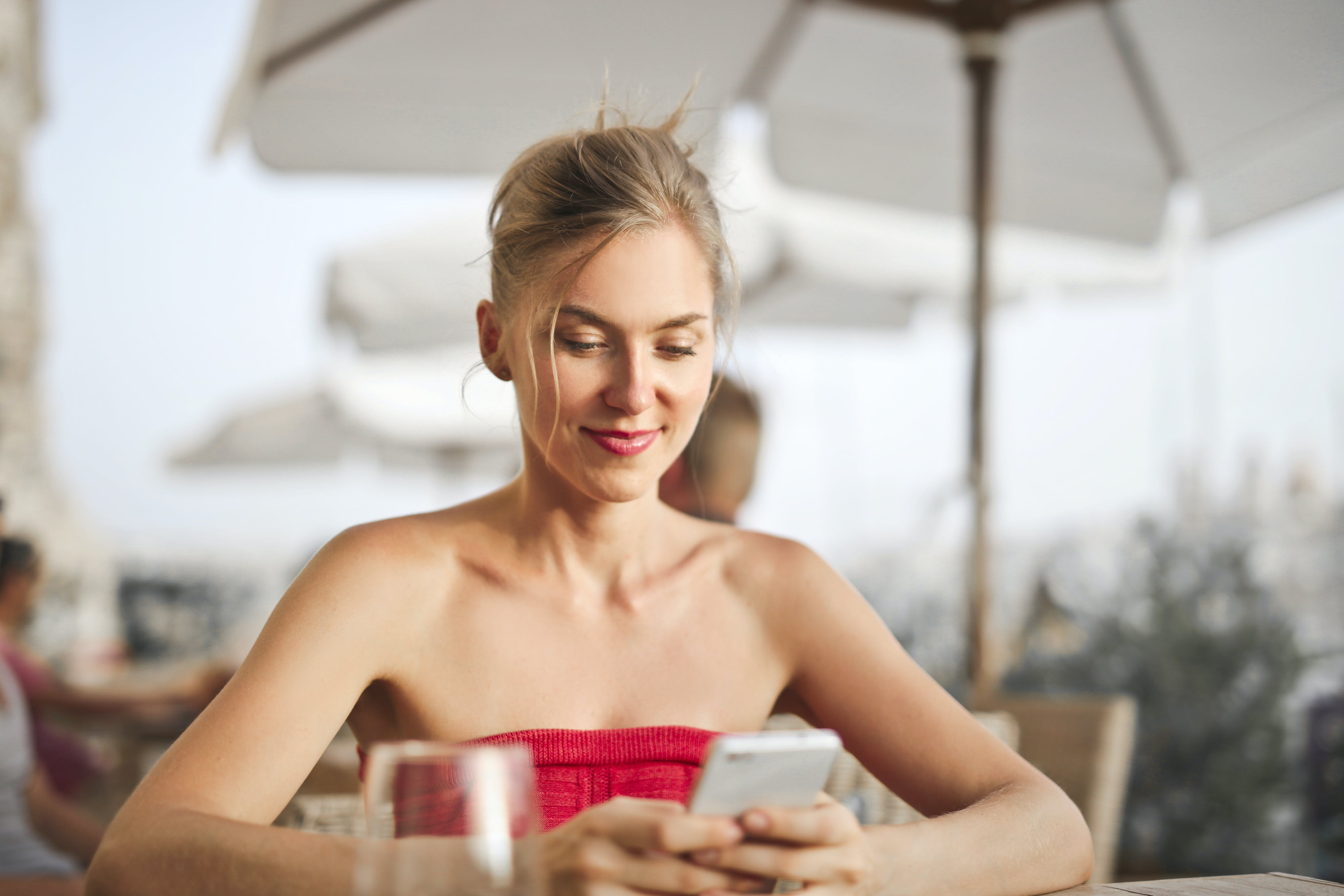Woman Sitting on Chair While Holding Smartphone