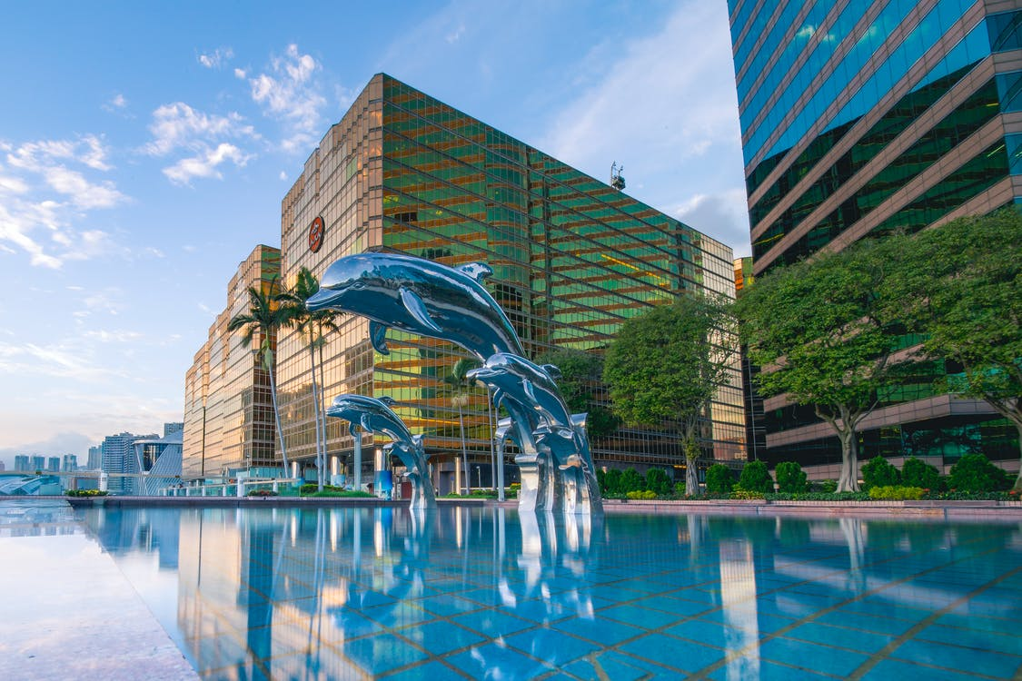 Three Blue Dolphins Statue Front of Water Near Building