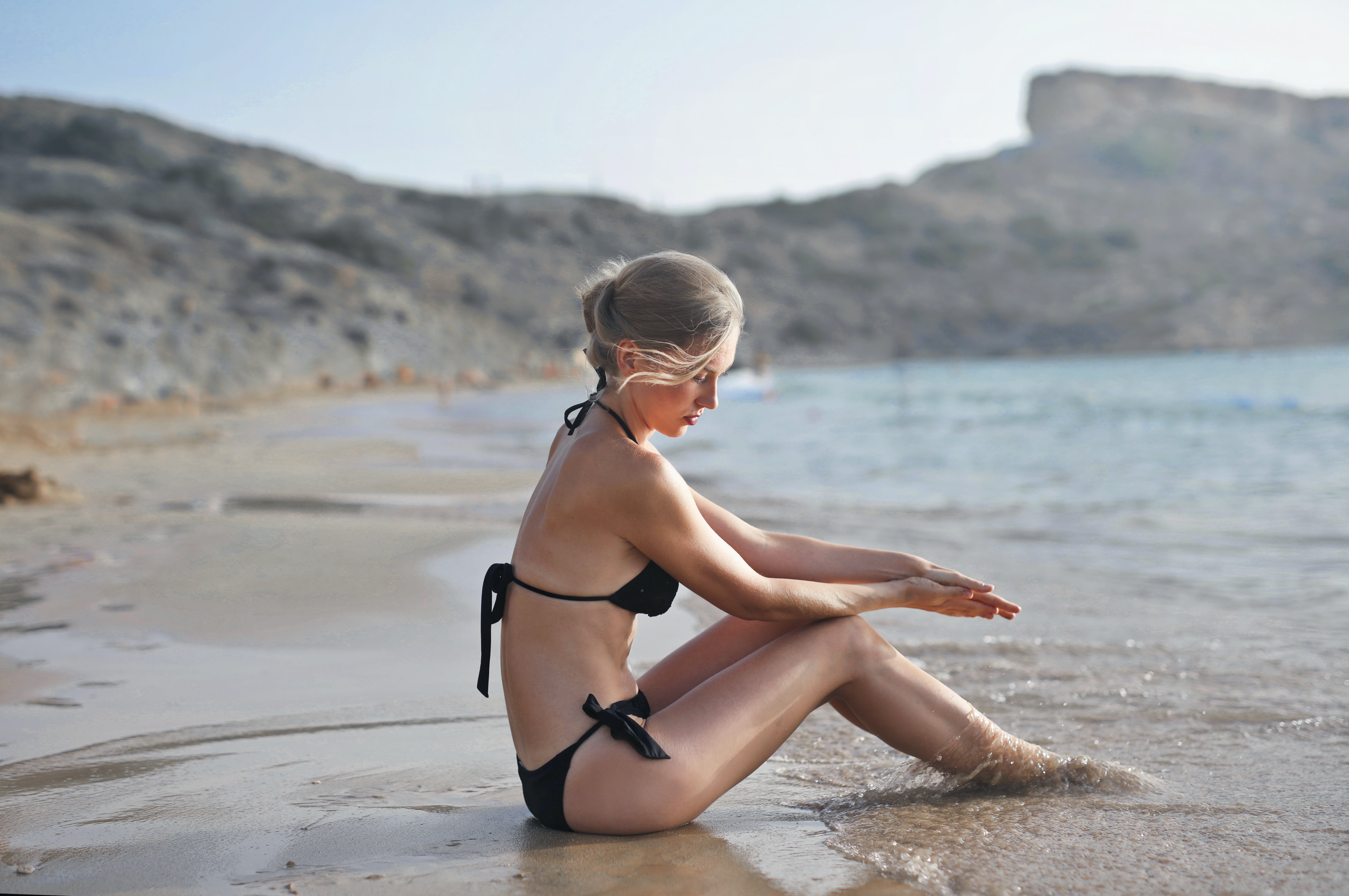 Woman in Black Bikini Sitting on Sand Near Seashore during Faytime