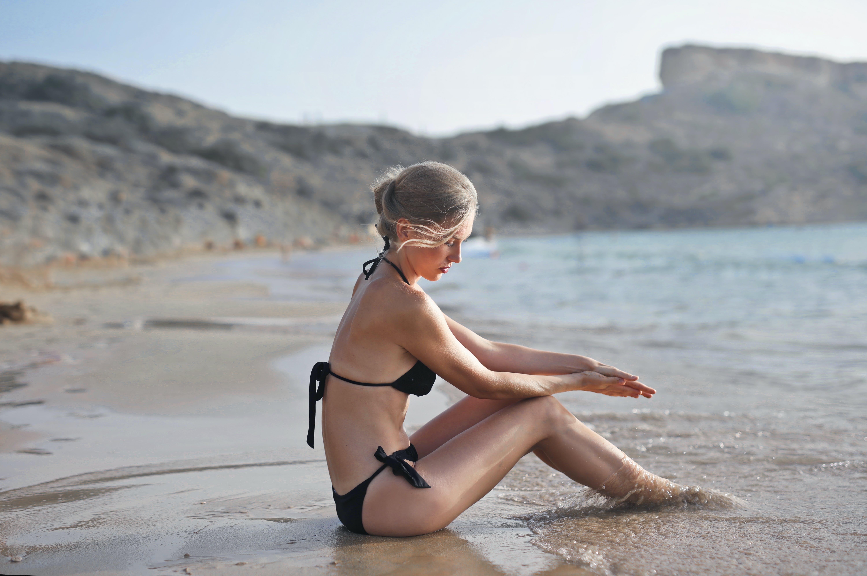 Woman in Black Bikini Sitting on Sand Near Seashore during Faytime