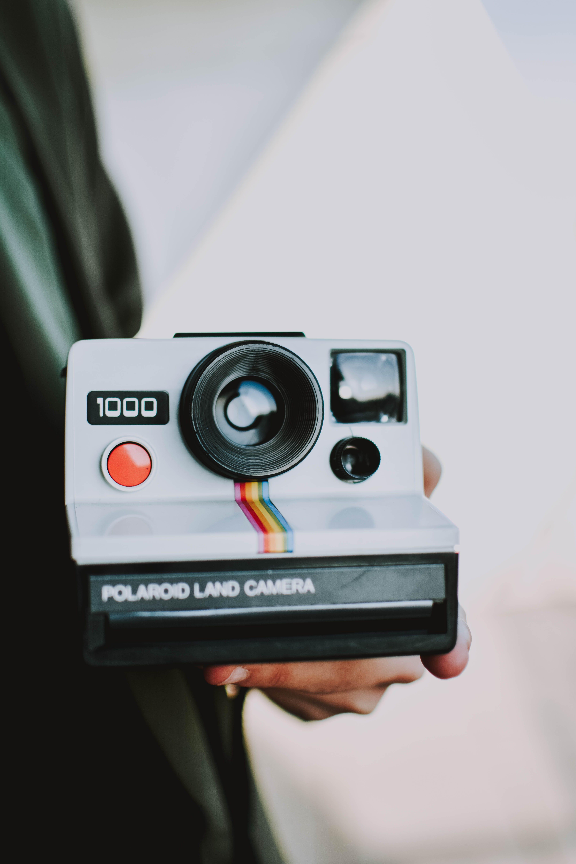 Person Holding Gray Polaroid Land Camera