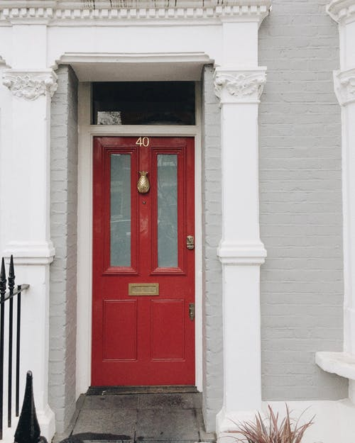 Red exit door in old building of modern city