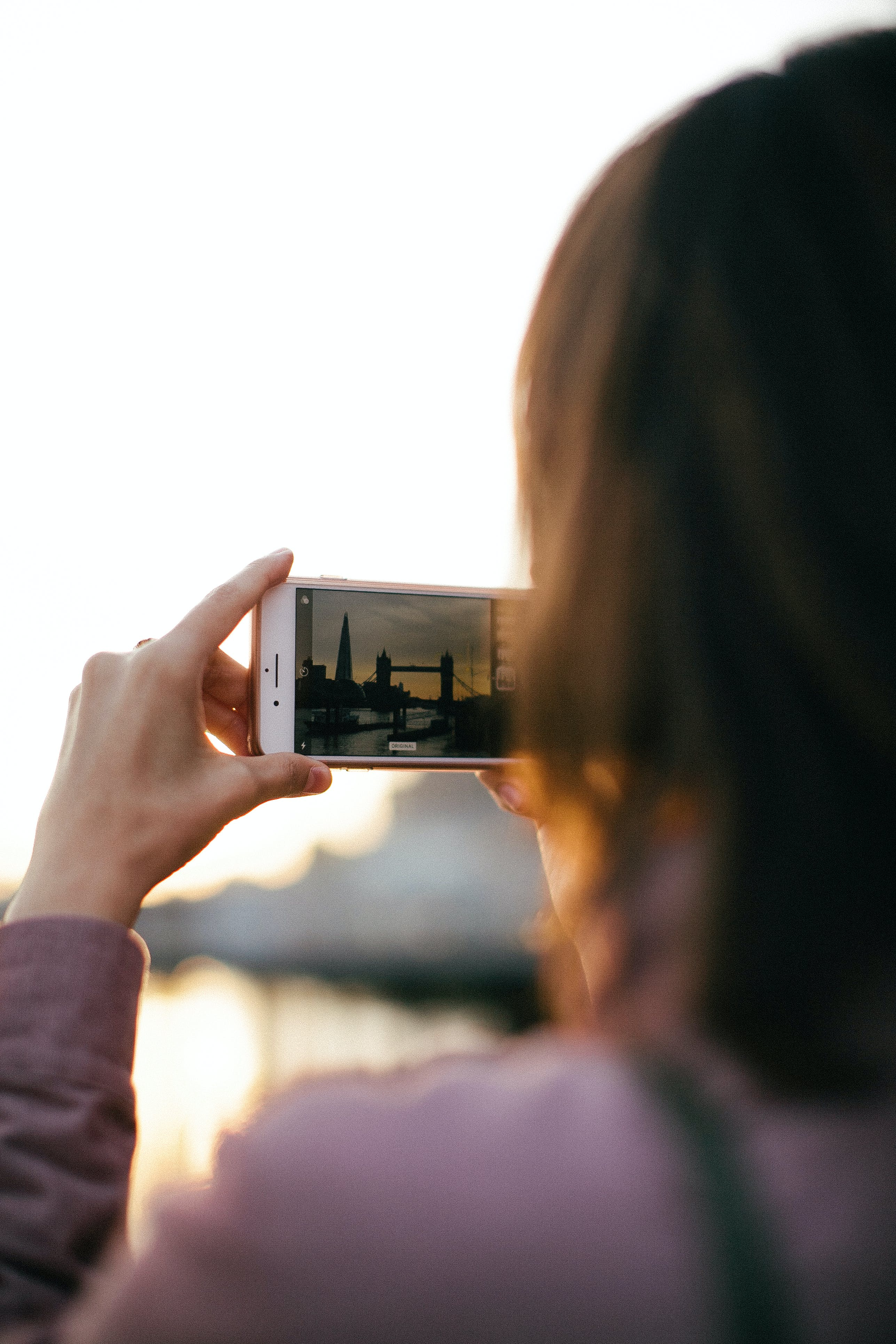 Person Holding White Smartphone While Capturing Tower Bridge at Golden Hour