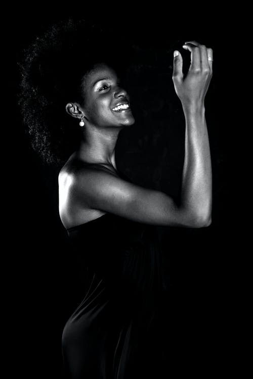 Grayscale Photo of Smiling Woman Wearing Dress