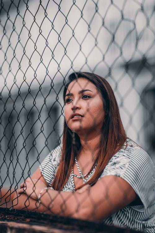 Shallow Focus Photography of Woman Leaning On Fence