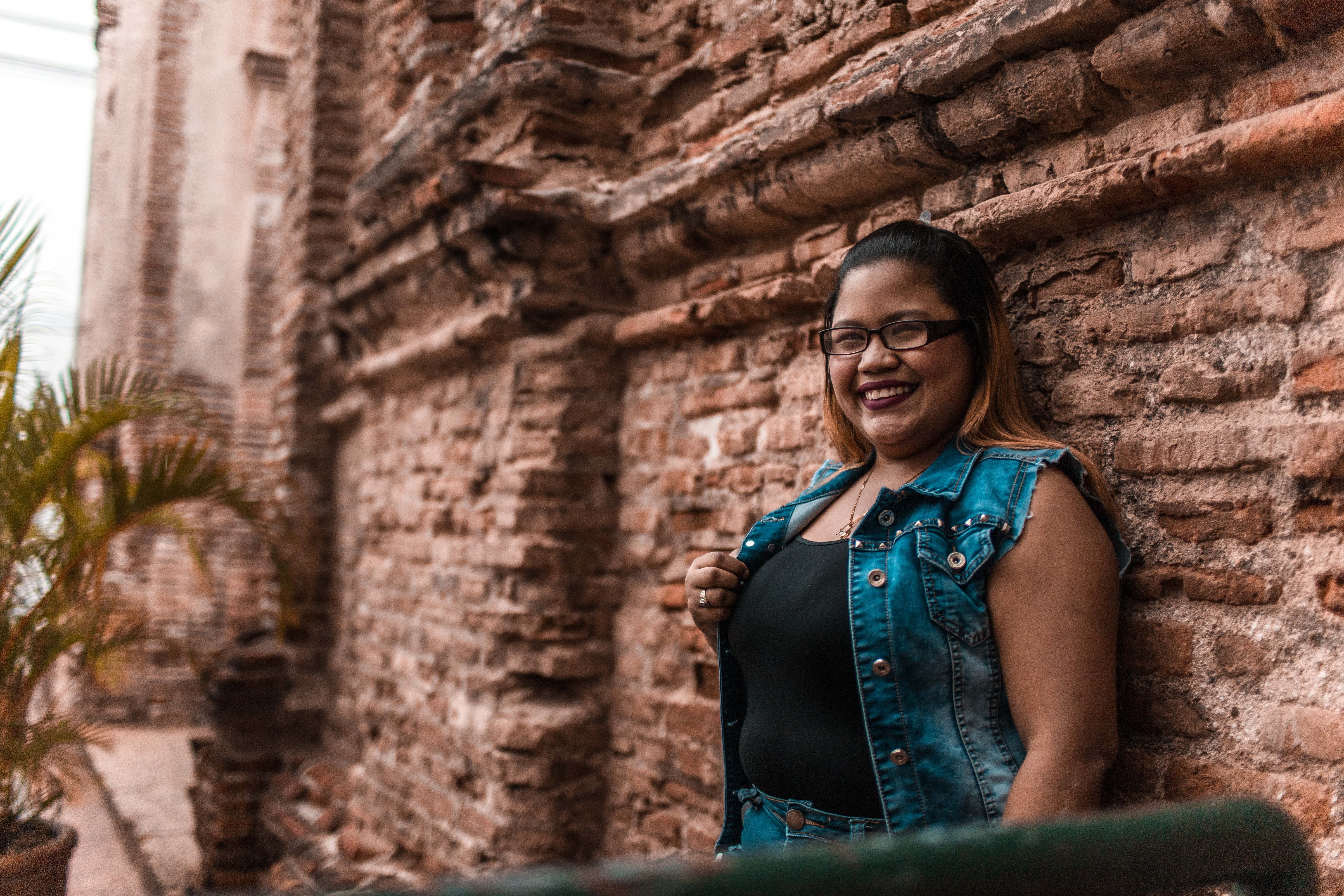 Woman Leaning on Brown Brick Wall