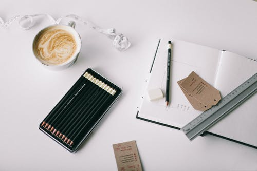 Flat Lay Photography of Grey Ruler on White Book
