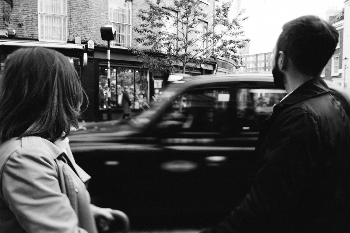 Grayscale Photography Man and Woman Standing While Cars on Road Near Buildings
