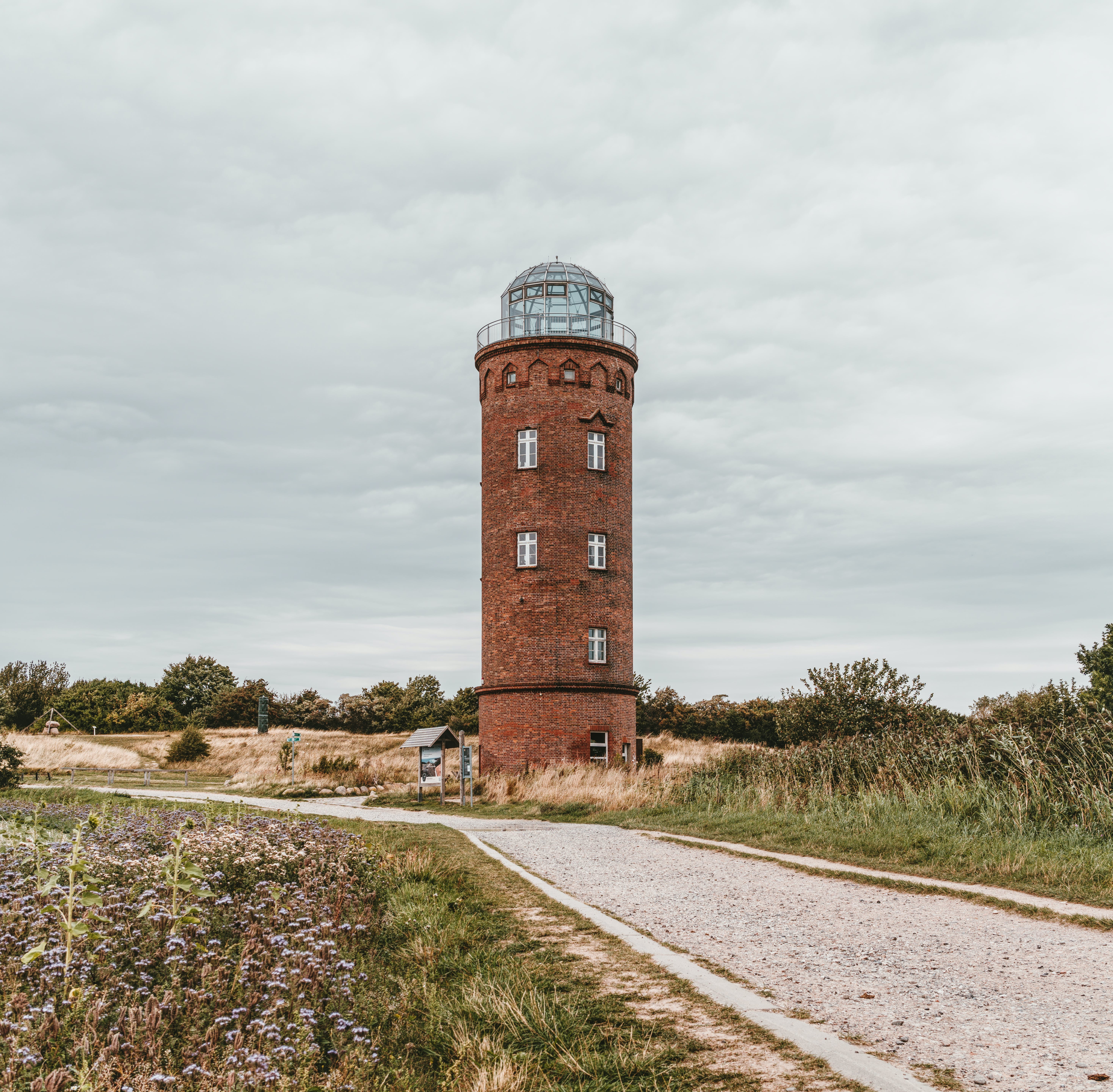 Round Brown Lighthouse Near Road Under White Cloudy Skies