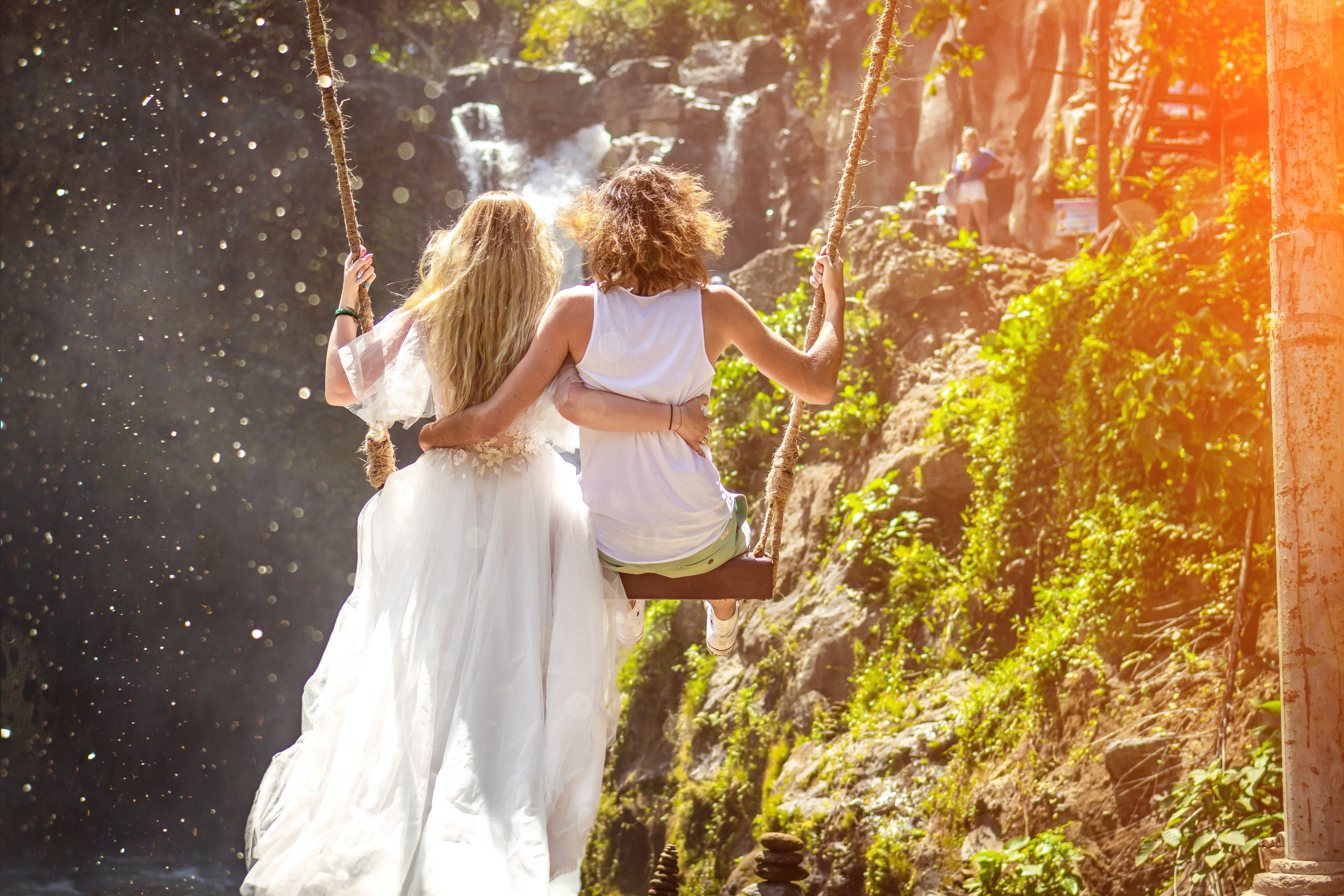 Woman and Woman Riding Wooden Swing in Front of Rock Formation
