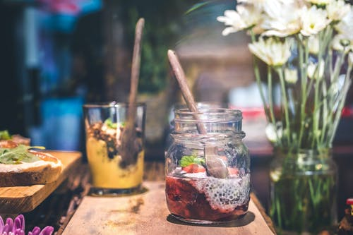 Slice Fruit in Clear Glass Jar Above Brown Wooden Table