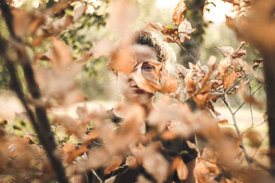 Woman Standing in Front of Brown Leafed Trees
