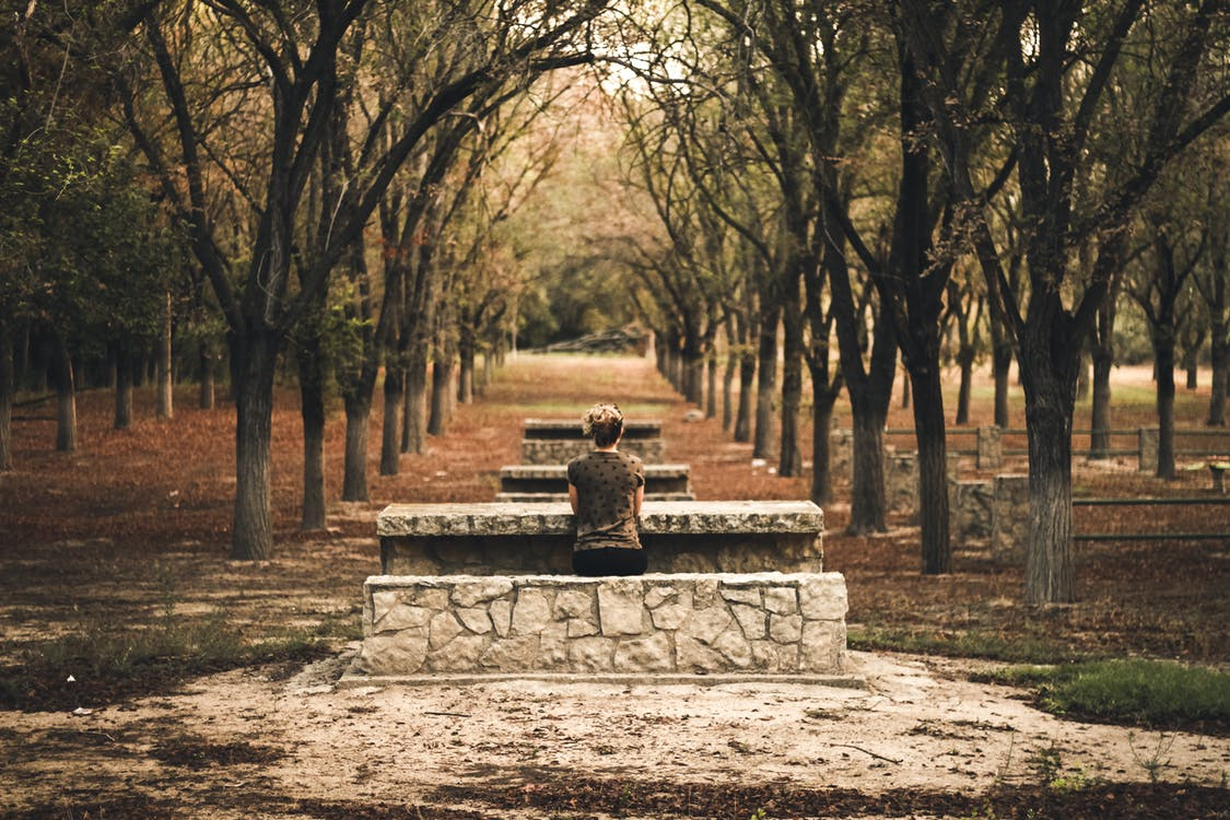 Person Sitting on Stone Bench