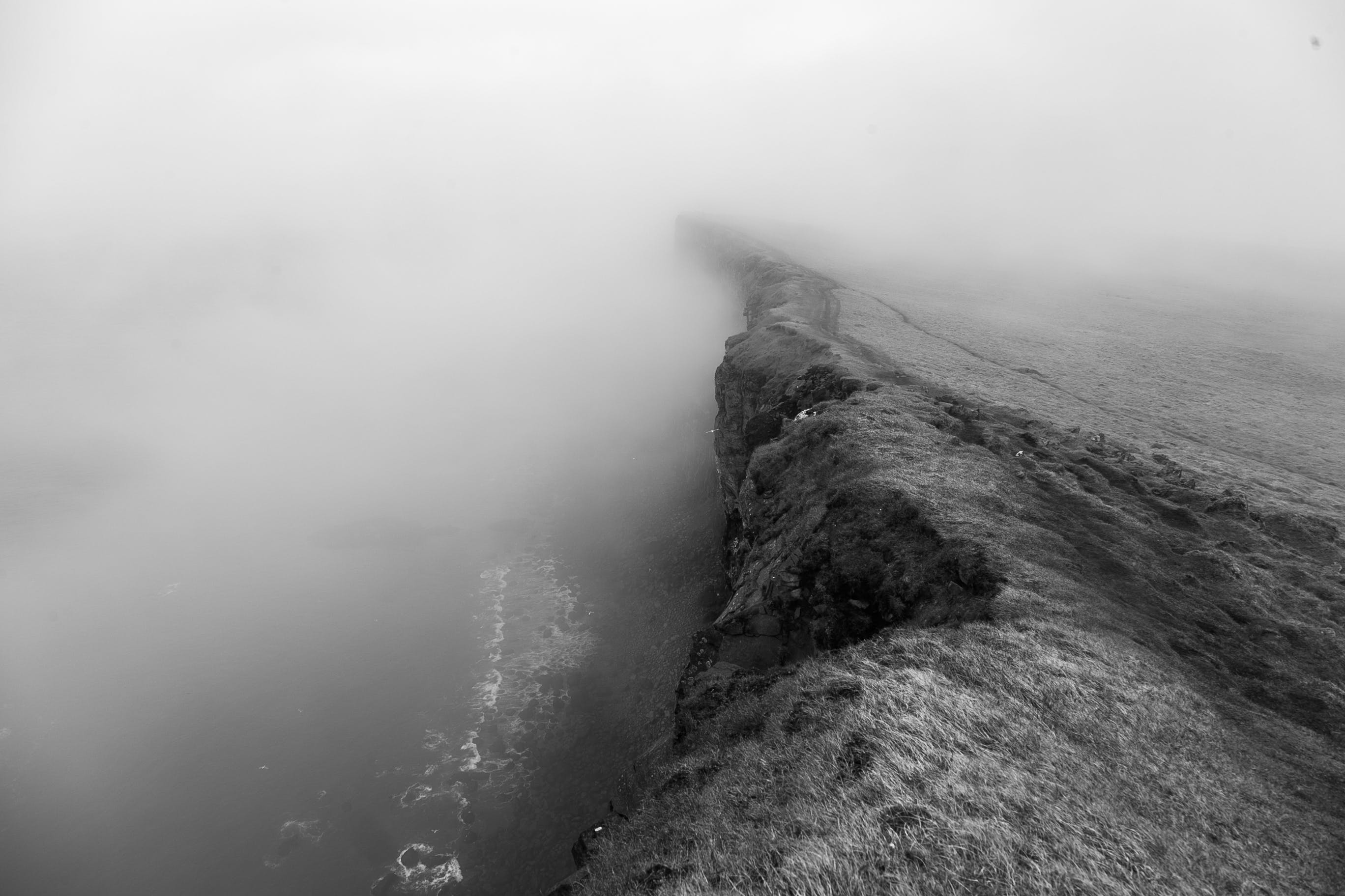 Grayscale Photo of Cliff Near Body of Water