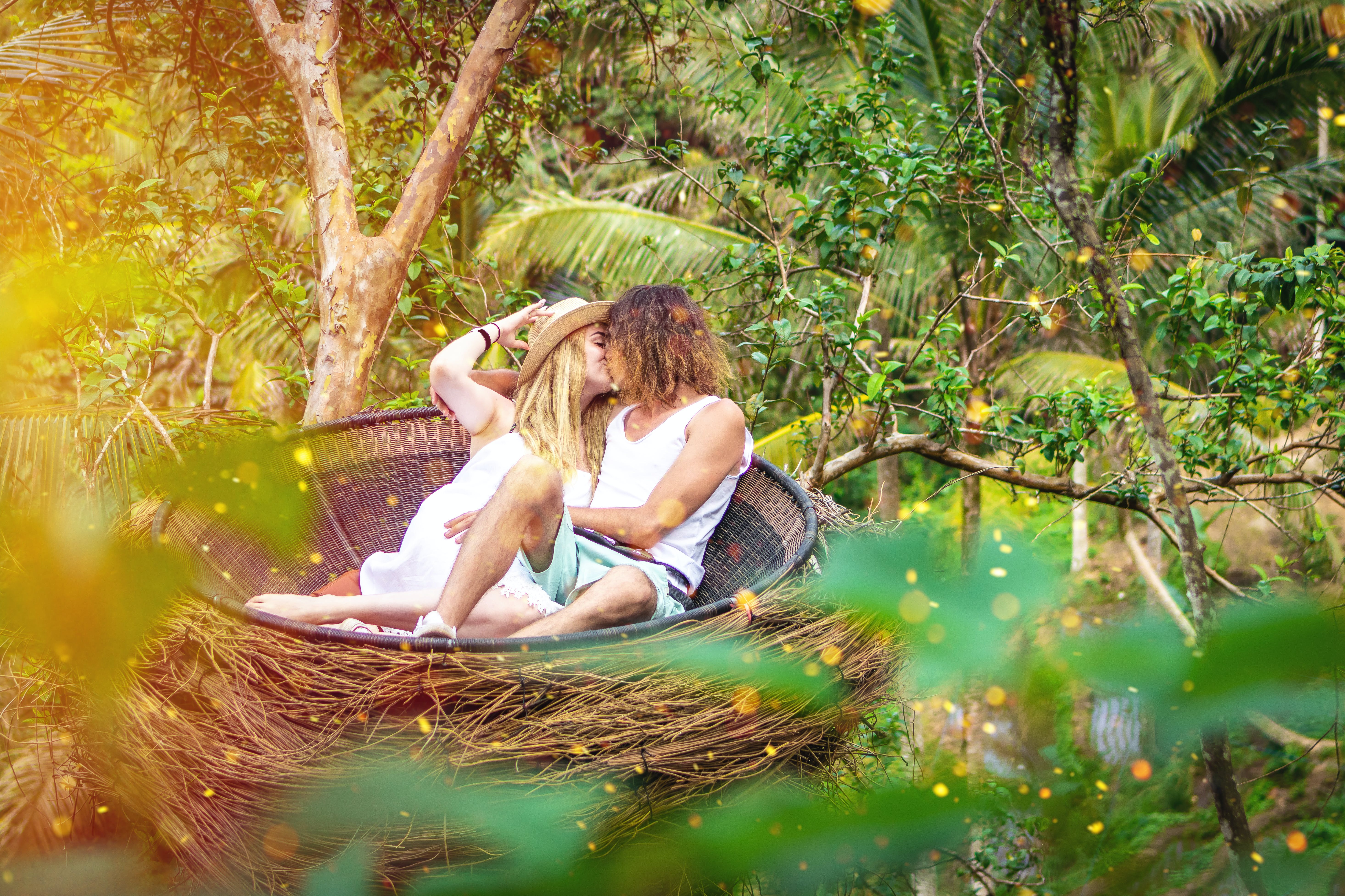 Man and Woman Kissing While Sitting in Round Brown Nest