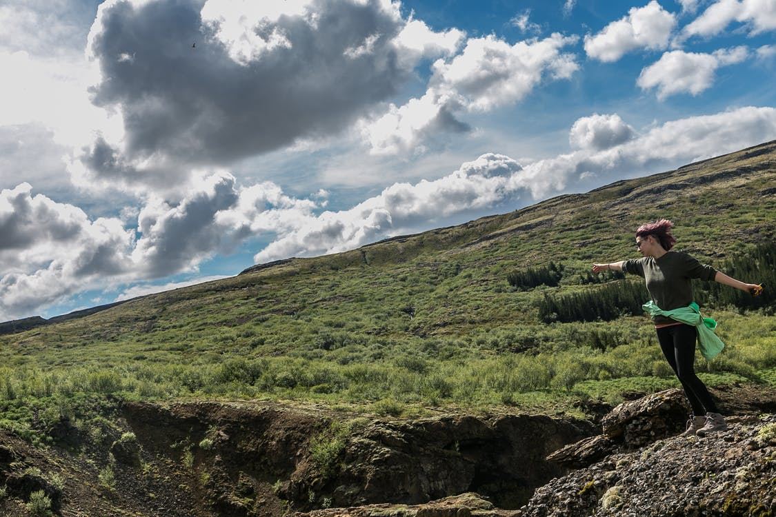 Woman Trekking on Green Grass Covered Hill