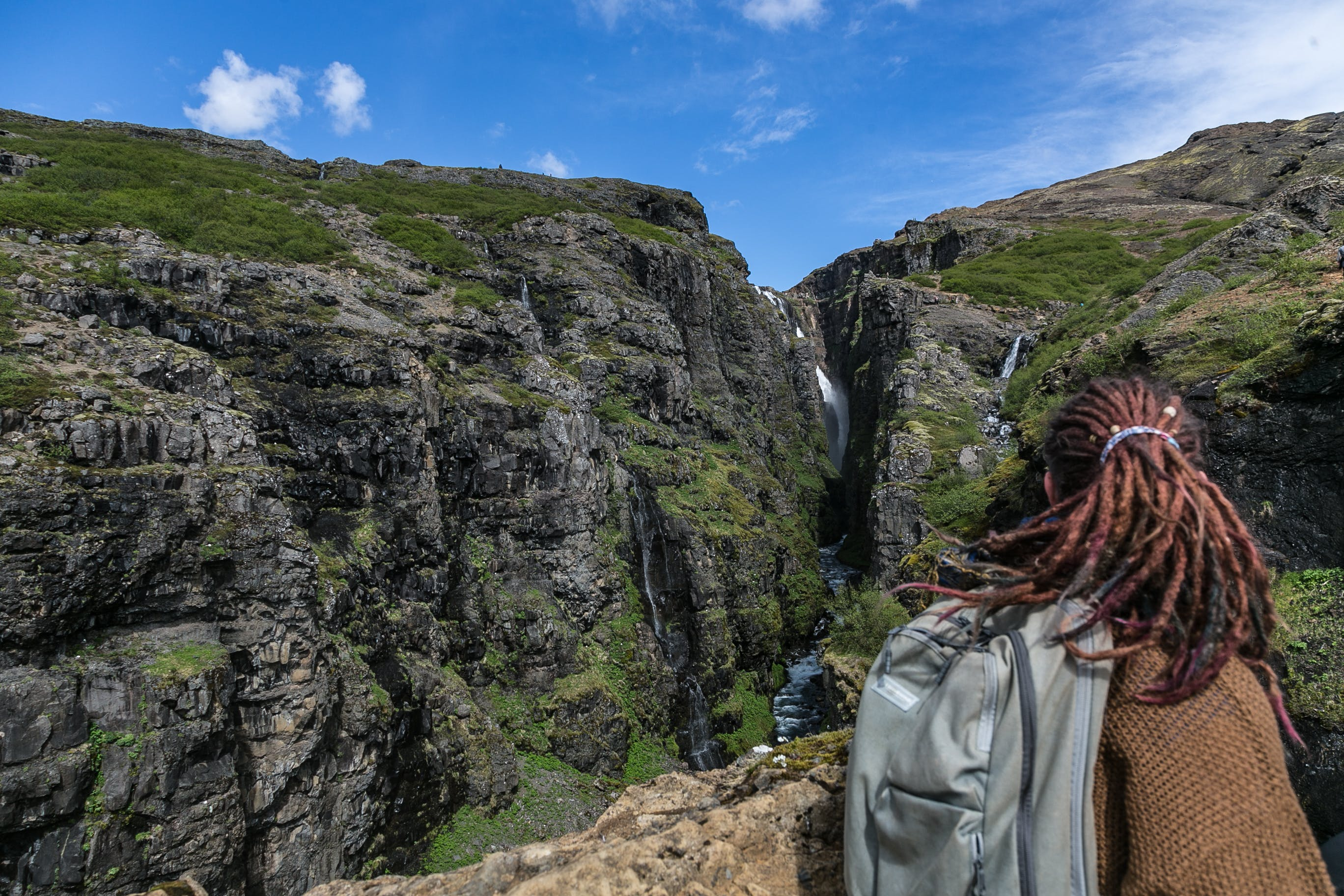 Person Wearing Brown Sweater and Grey Backpack With Brown Hair Dreadlocks on Top of Mountain Overlooking Waterfalls