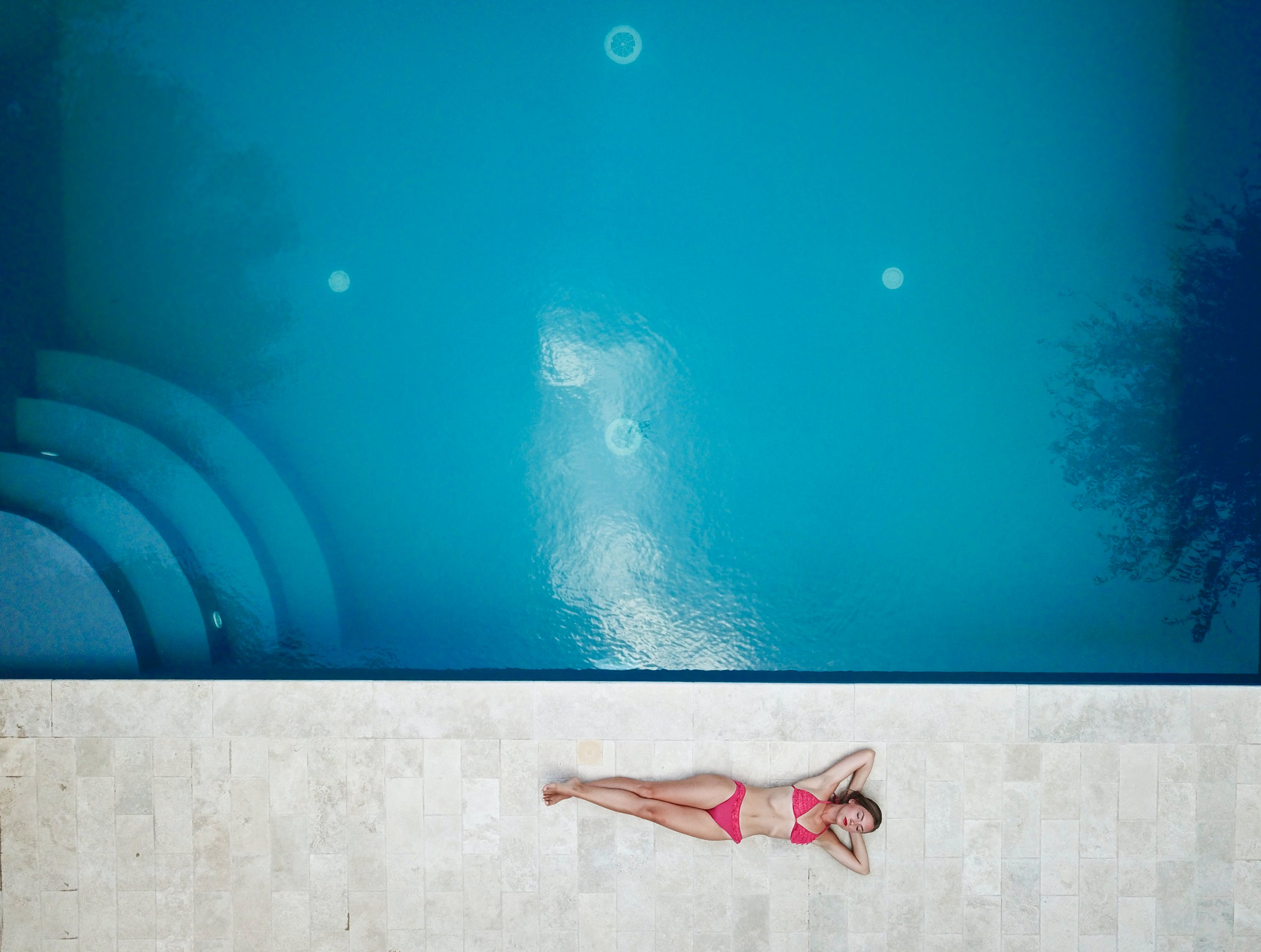 girl lying on the floor near pool