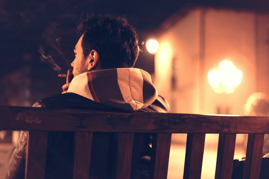Shallow Focus Photography of Man Sitting on Bench While Smoking