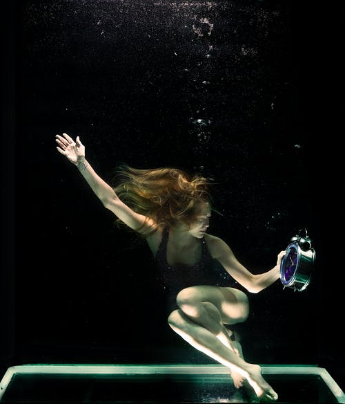 Woman Underwater Holding Round Gray Clock