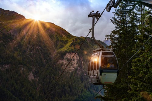 Selective Photo of Cable Car Surrounded by Tree and Hill